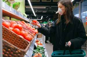 woman in face mask shopping in supermarket